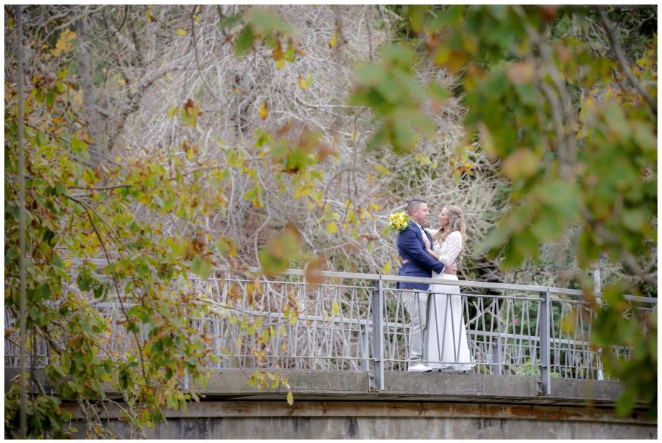 Bride and groom buy Puhoi Village historic bridge over the river.