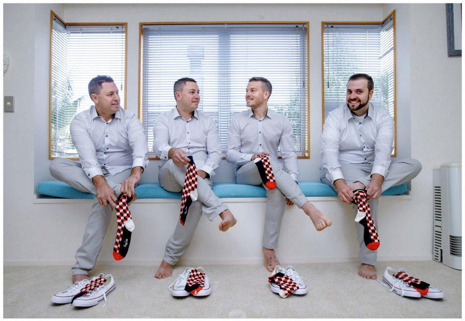 Groomsmen get ready for wedding wearing matching socks