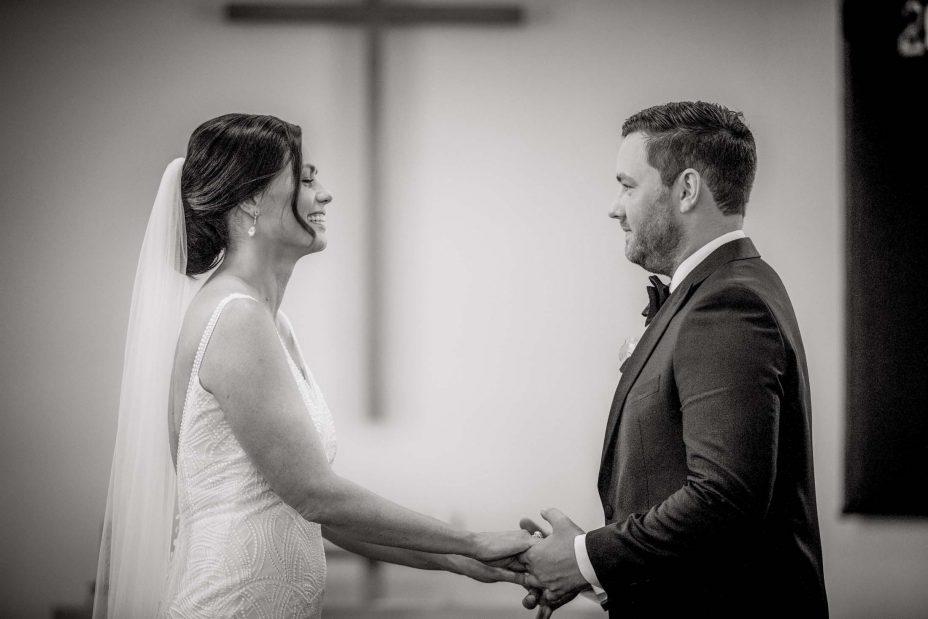 Happy bride looks into groom's eyes during wedding ceremony Saint Cuthbert's College chapel Auckland