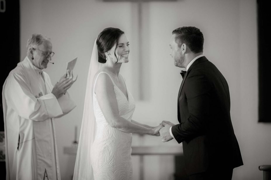 Bride looks into groom's eyes during wedding ceremony Saint Cuthbert's College chapel Auckland