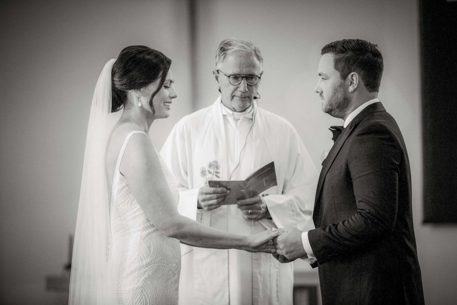 Smiling bride looks down at wedding on groom's finger and makes vows during wedding ceremony Saint Cuthbert's College chapel Auckland