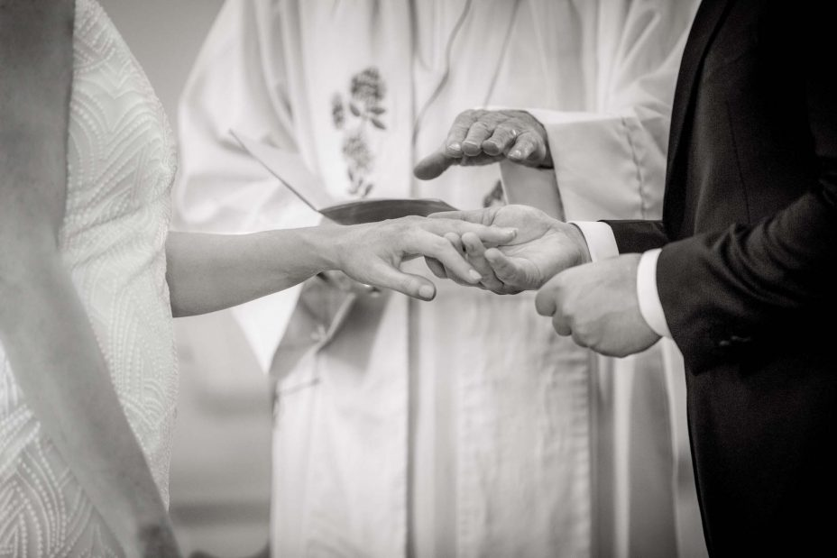 Celebrant blesses wedding rings during ceremony Saint Cuthbert's College chapel Auckland