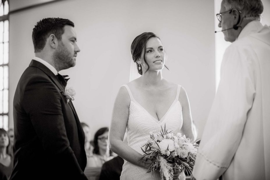 Bride and groom listen to celebrant during their wedding ceremony Saint Cuthbert's College chapel Auckland