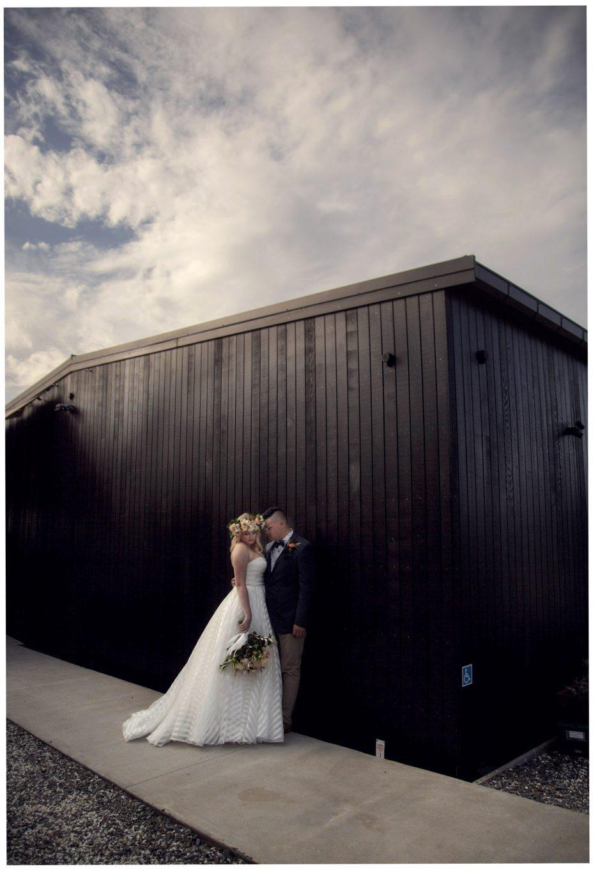 Bride and groom next to The Barn Wedding reception venue at The Hunting Lodge Waimauku