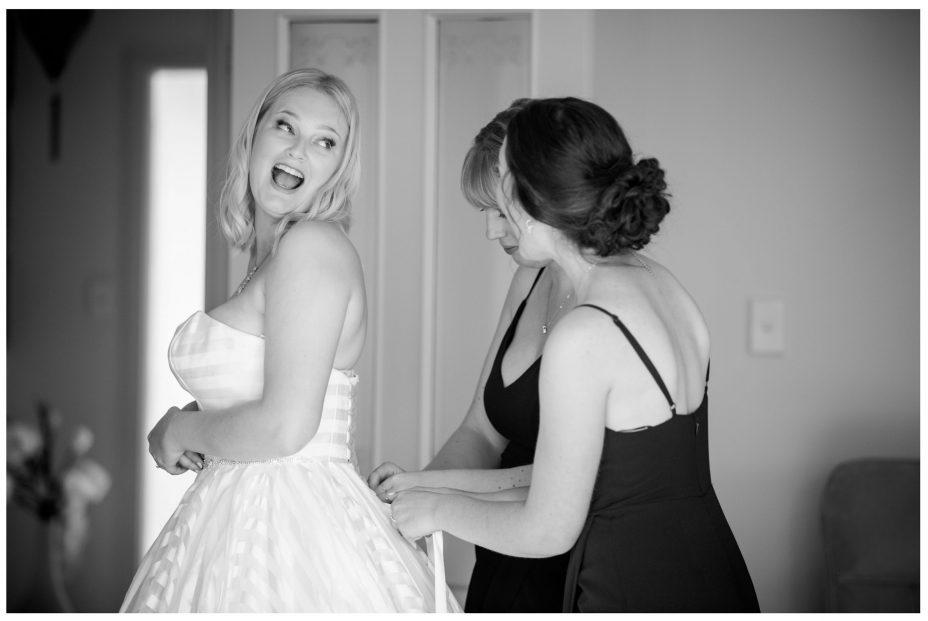 Bride laughs as bridesmaids fasten her wedding dress