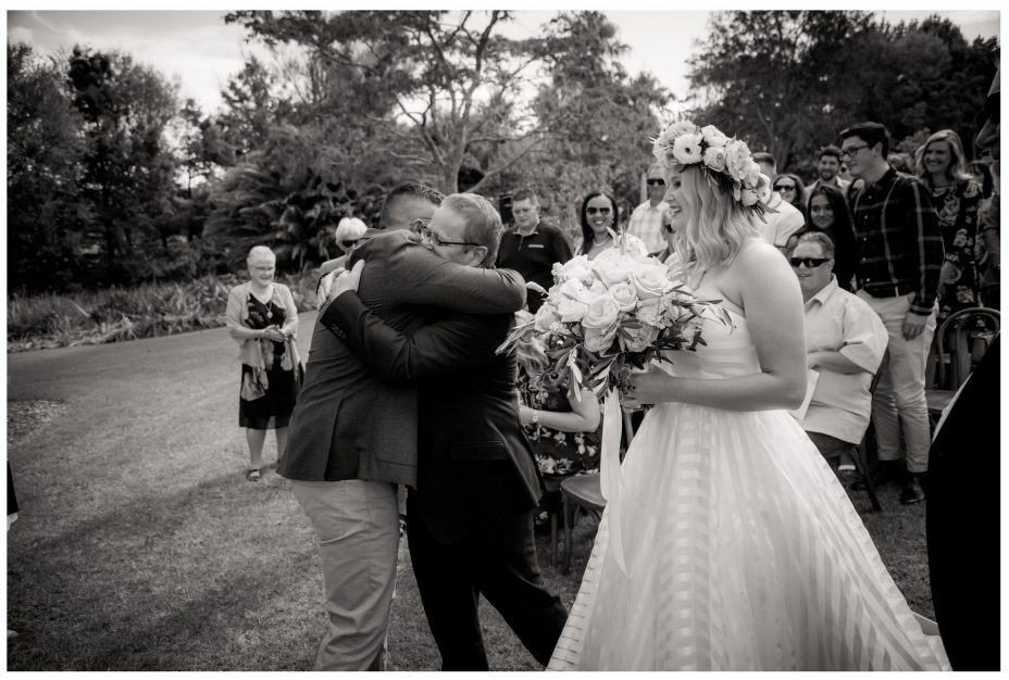 Bride's father hugs groom just before the wedding ceremony