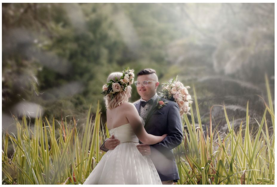 Bride and groom backlit by evening sun in the long reeds.