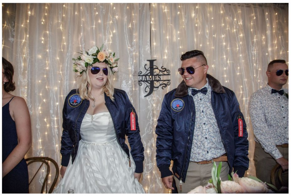 Bride and groom wearing Top Gun flying jackets and Ray Ban Aviator sunglasses