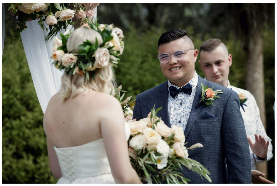 Groom smiles into his bride's eyes as they make their wedding vows. Happy, joyful love filled photo.
