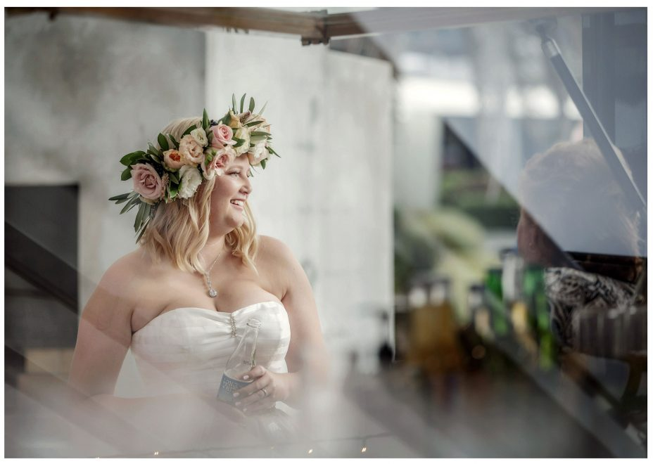 Bride ion flower crown photographed through a glass window, arty photo