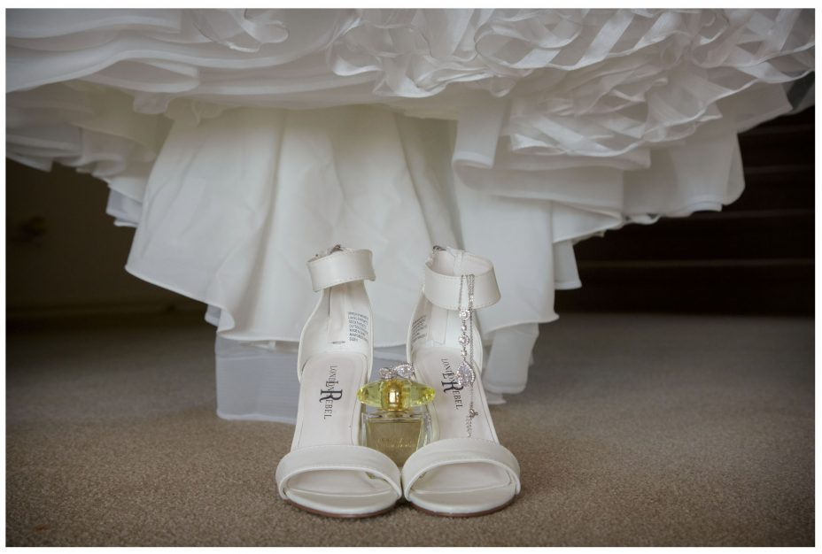 Still life photo, wedding dress with shoes , perfume and jewellery.