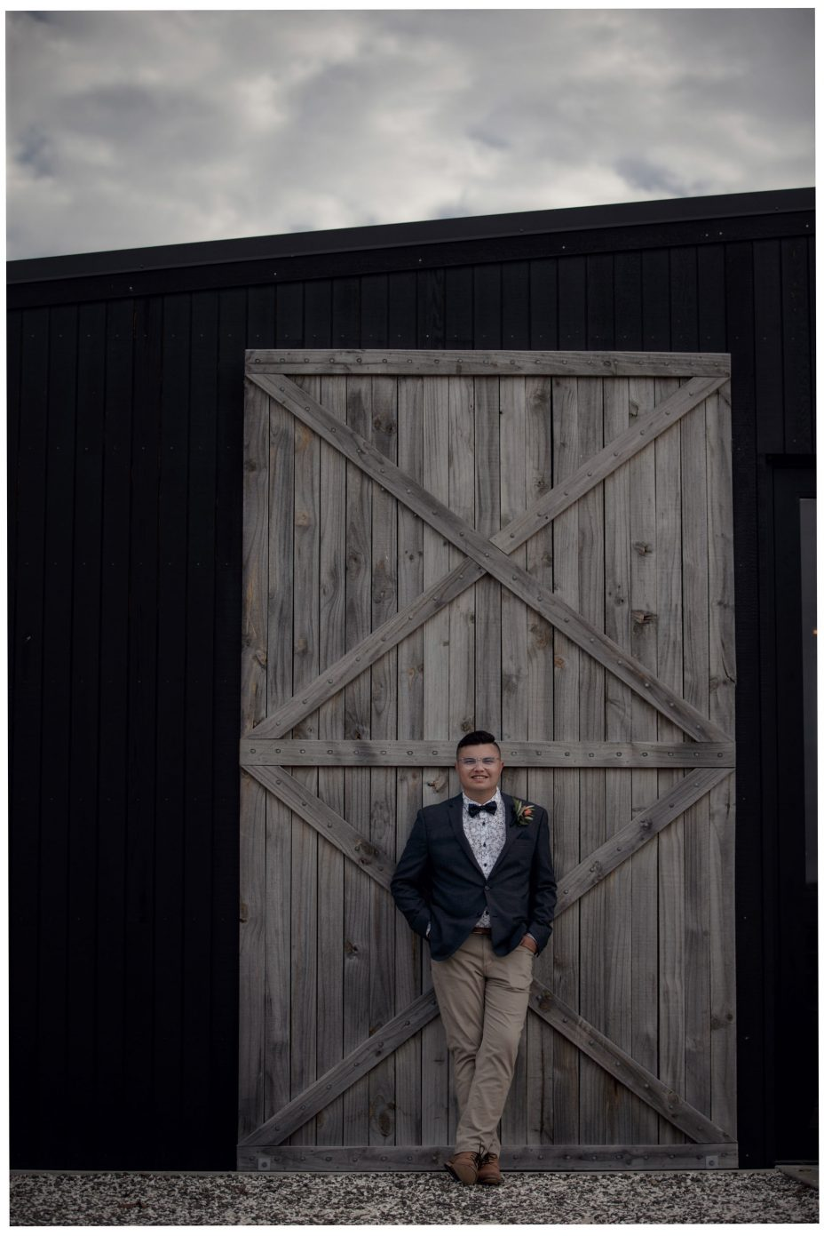 Bride groom posed against the large wooden doors of The Barn wedding reception venue at The Hunting Lodge Winery