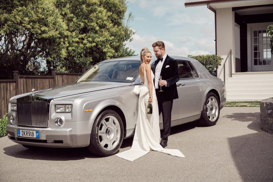 Bride groom with Dom Perignon Champagne pose by Rolls Royce weding car at The Northern Club Auckland