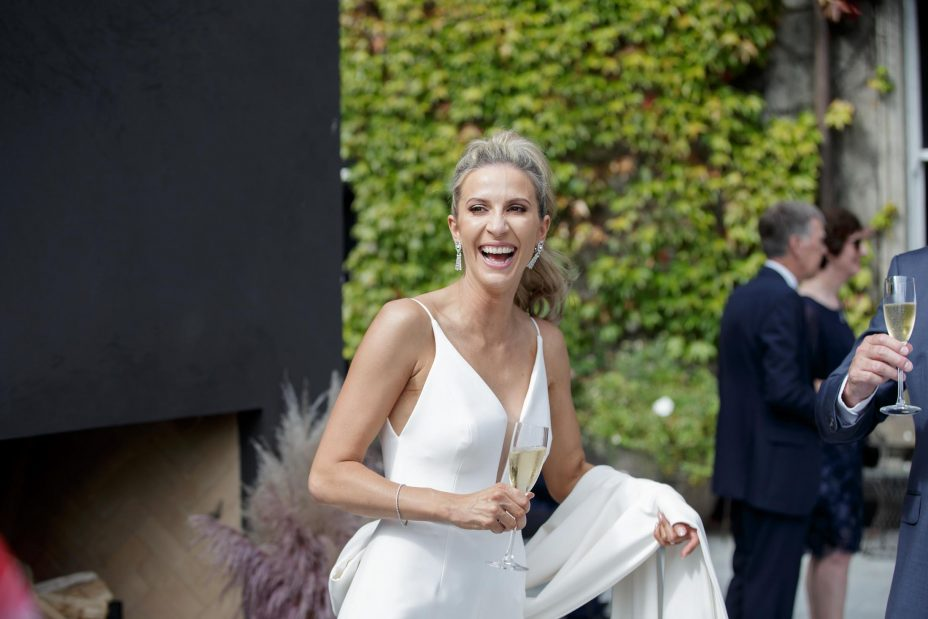 Bride in white ivory pant suit carries her train and laughs