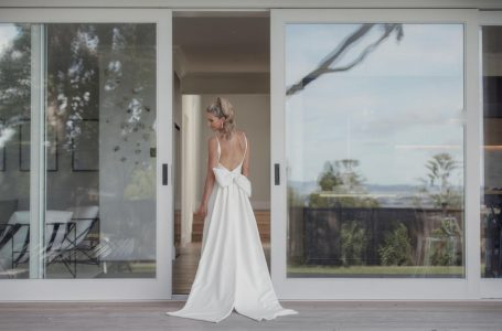 Cute slim bride wearing ivory pant suit and Mi Piachi cream leather boots. Wedding photo at The Northern Club Auckland