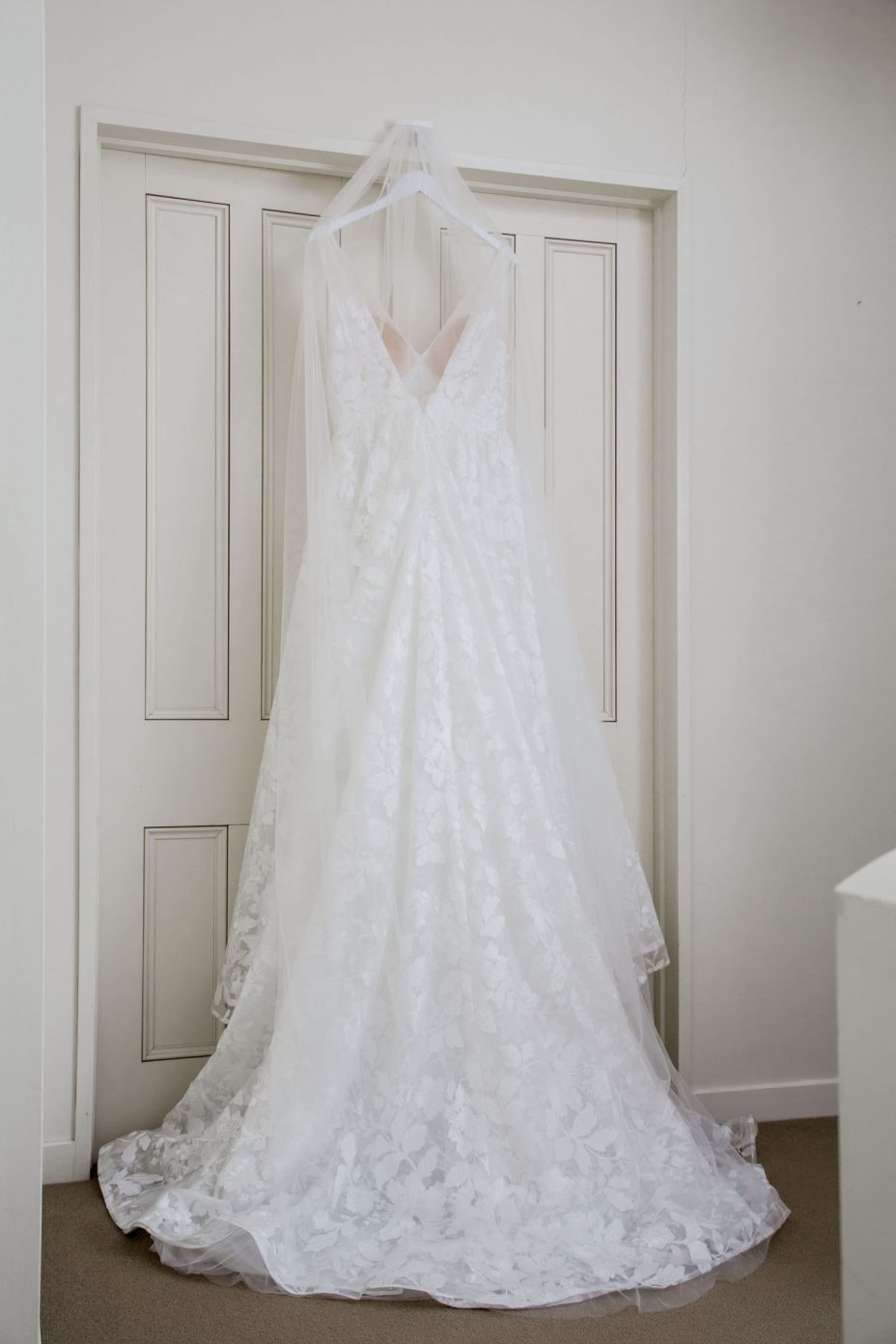Lace wedding gown hanging from dorway