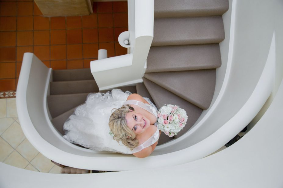 Bride in wedding dress posing on curved staircase