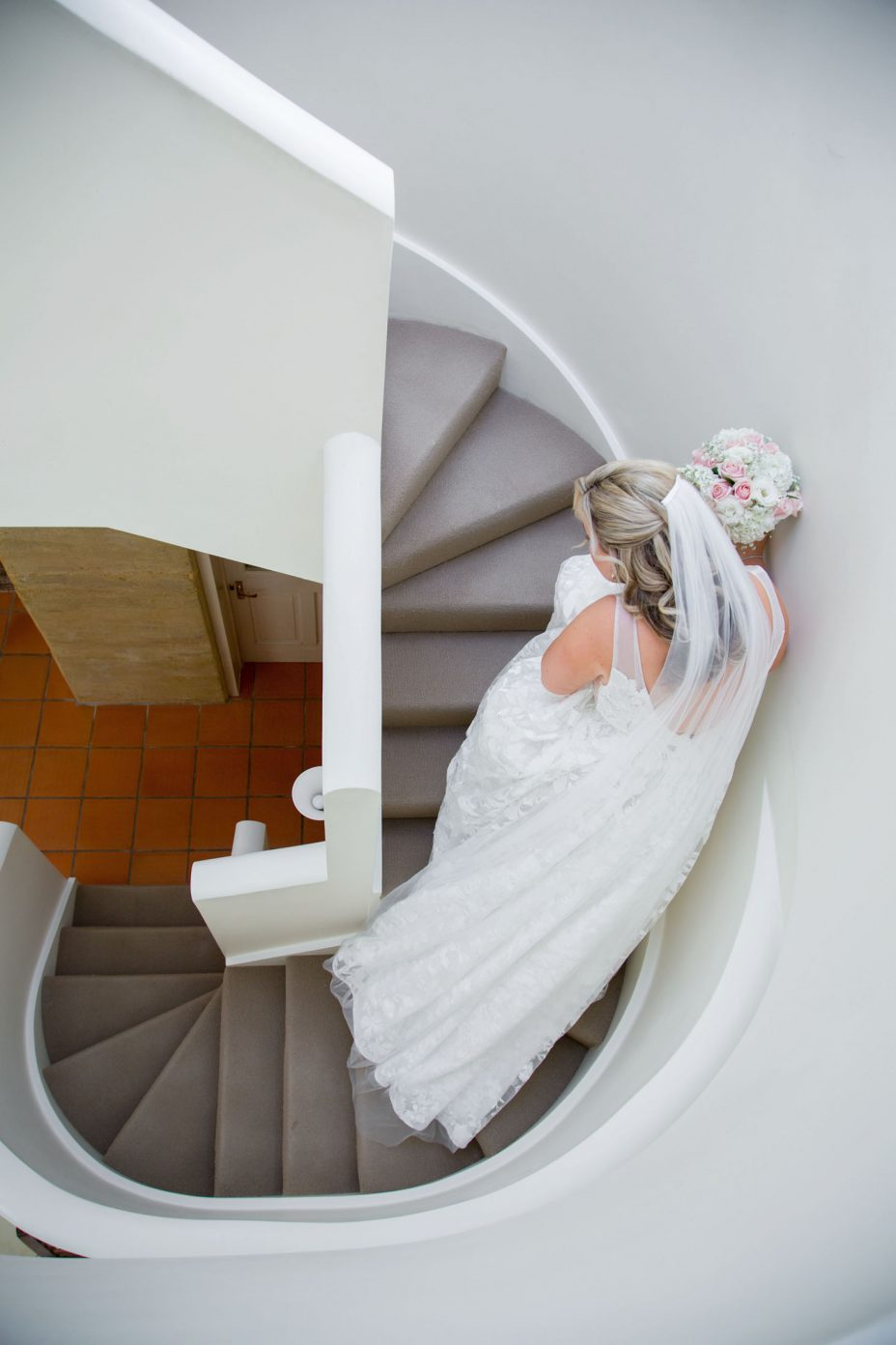 Bride in wedding dress walking down curved staircase