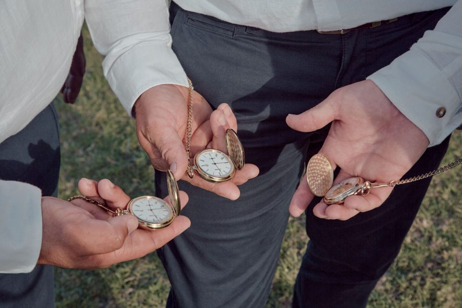 Groomsmen show their pocket watches