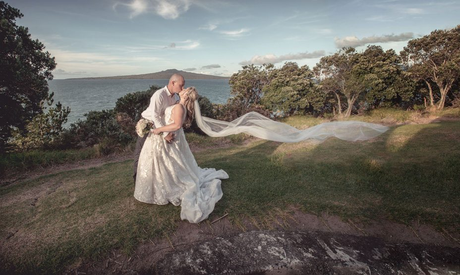 sunset wedding photo of bride and groom kissing in front of Rangitoto at fort takapuna