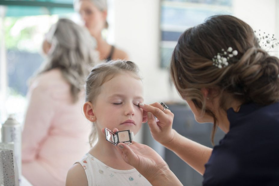 Cute flower girl has wedding makeup applied