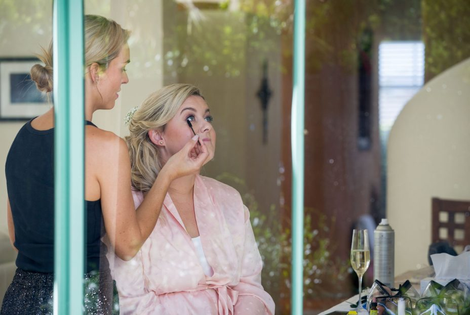 hoto through window as bride has her wedding make up applied