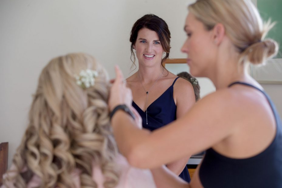 hoto bridesmaid look on as bride has her wedding make up applied