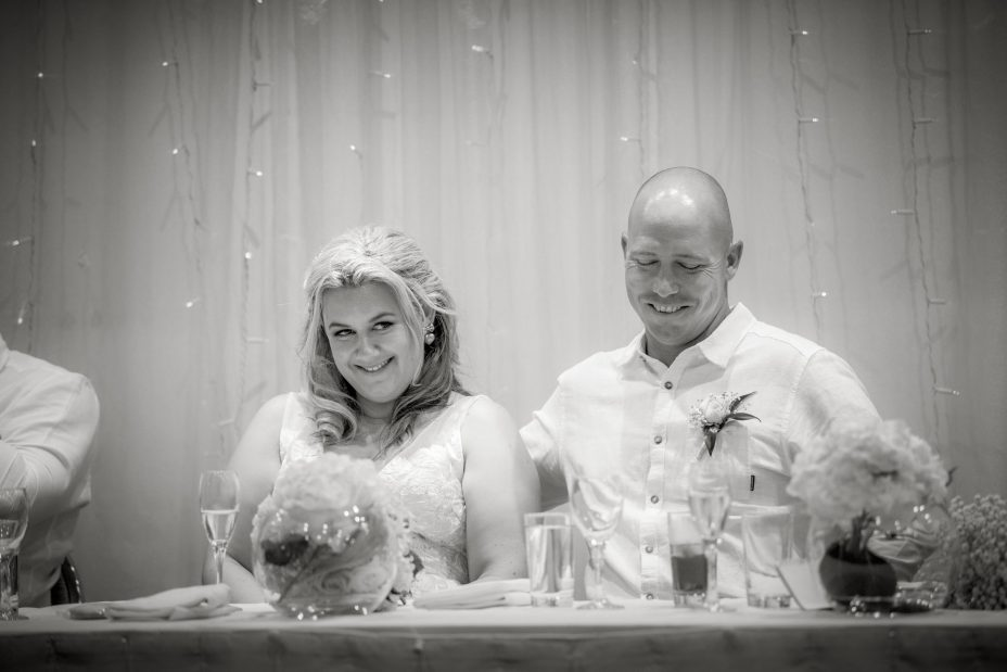Bride and groom laugh at speeches blak and white photo at Mchugh's Cheltenham