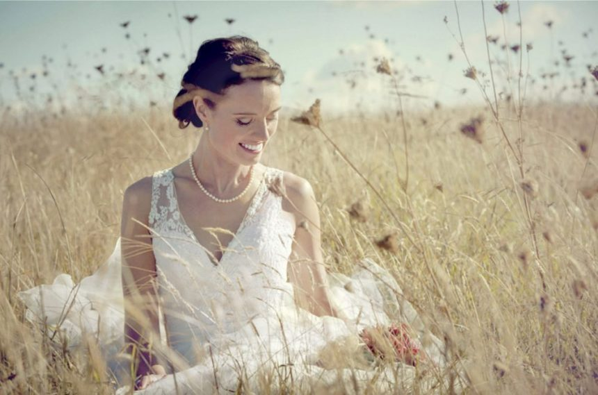 Auckland-Bride-white-wedding-dress-sits-a-field-of-long-grass-on-a-summer-day