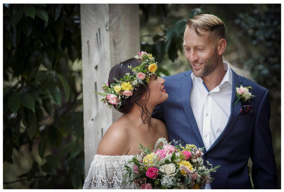 Bride with lace wedding dress and flower crown and groom in blue suit gaze into each others eyes, outdoor wedding ceremony, Kumeu Valley Estate