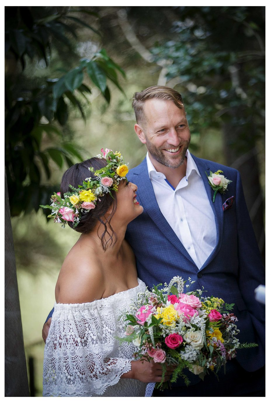 Bride with lace wedding dress and flower crown look lovingly at groom in blue suit gaze into each others eyes, outdoor wedding ceremony, Kumeu Valley Estate