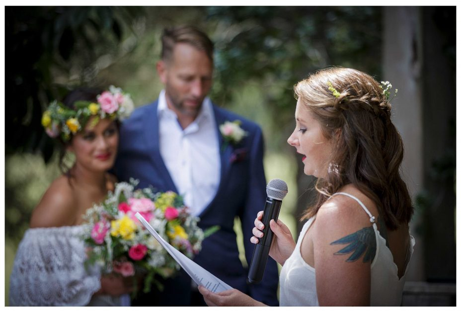 Wedding guest reds poem at Kumeu Valley Estate wedding ceremony, Bride and goom lookk on with love