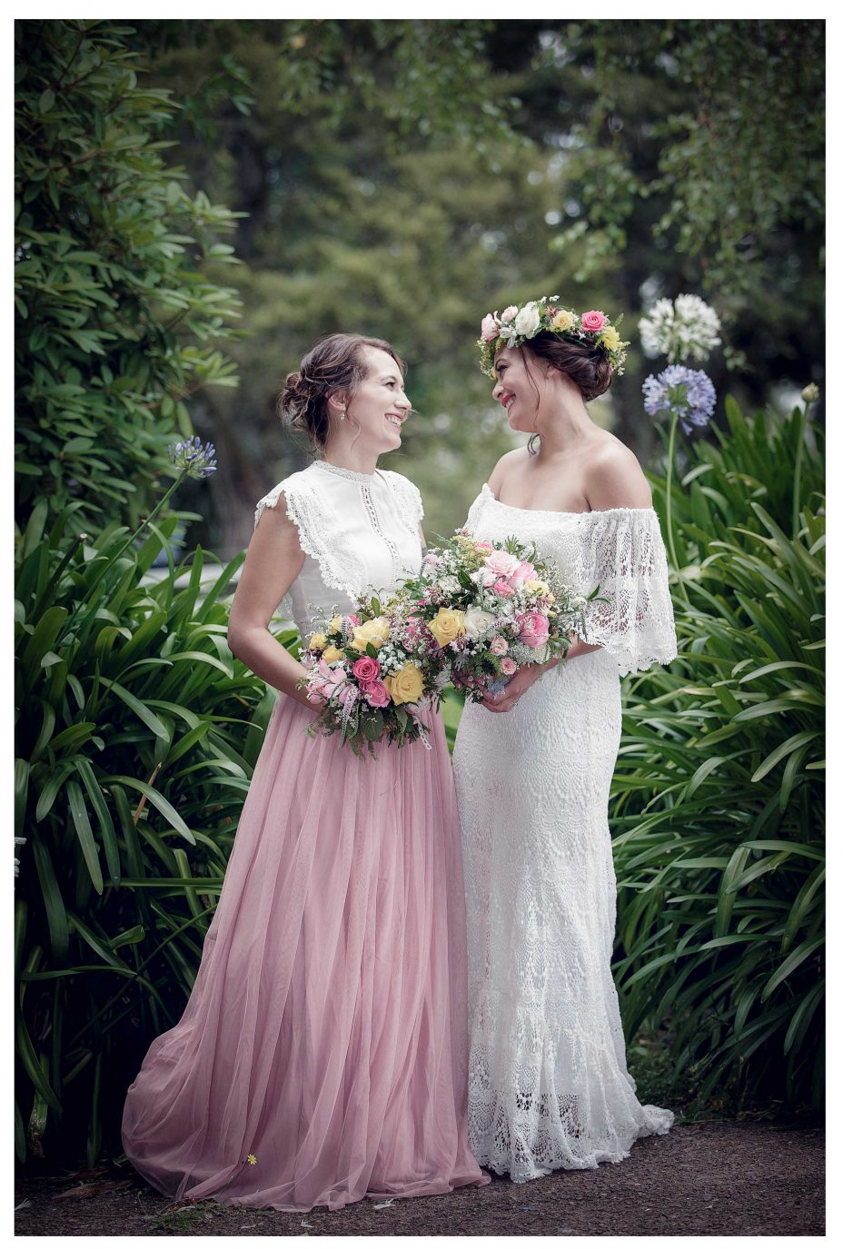 Bride in lace top ivory wedding dress with maid of honor in kumeu garden, Lichfields Cottages