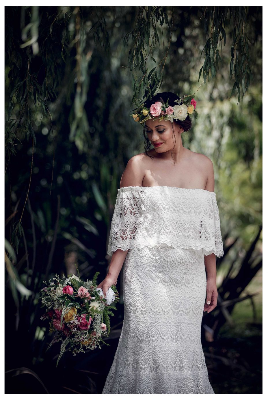 Bride in white lace top wedding dress in Kumeu garden, with wedding bouquet, Leaf and honey flowers