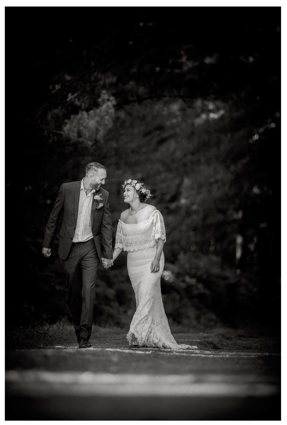 Bride and groom wlak hand in hand along Riverhead Forrest track, Kumeu Valley Esatte creative wedding photo