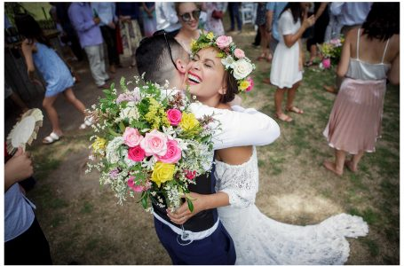Smiling bride hugs guest, Flower crown, Leaf and Honey Wedding flowers, Kumeu Valley Estate garden outdoor wedding