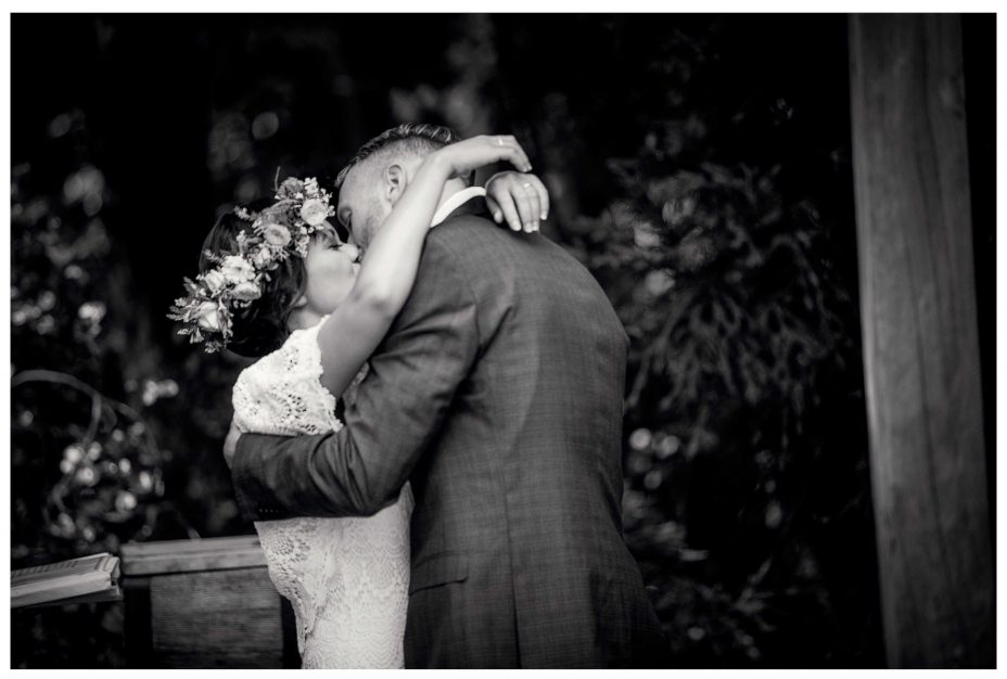 Bride with flower crown, Leaf and Honey wedding flowers, Kumeu Valley Esatte wedding Ceremony first kiss with groom.