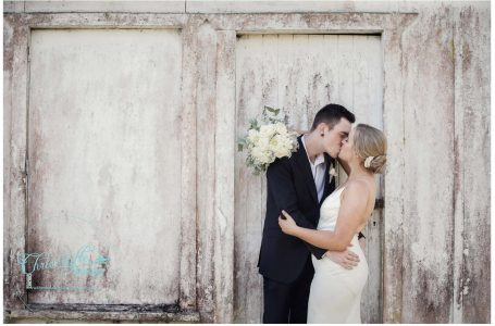 Bride in White backless weddding dress kisses her husband,groom, against rustic orchard outbuilding in Kumeu orchard,