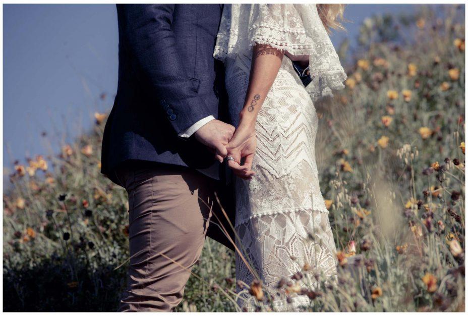 Bride in lacce wedding dress and groom hold hands, Muriwai Beach romantic runset weddimg photo